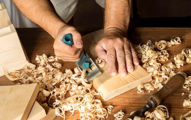 Timmerman die met zijn blote handen op hout werkt
