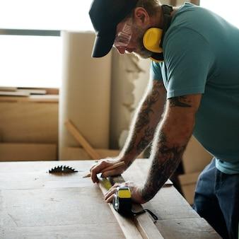 Timmerman die potlood en metingsband op hout gebruikt