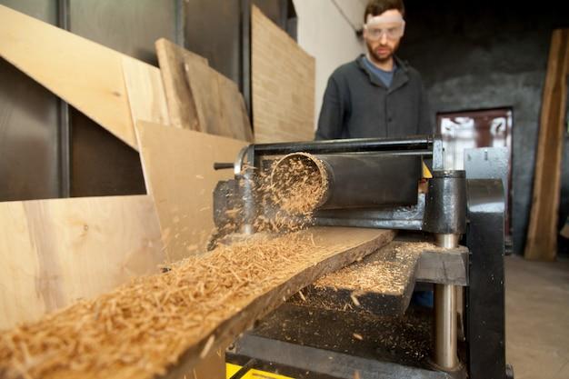 Timmerman die stationaire machtsplanner gebruikt, houten plank verwerken, zaagsel maakt