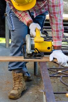 Timmerman die veiligheidsuitrusting draagt en houten plank met handzame cirkelzaag snijdt