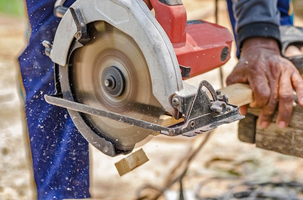 Timmerman gebruikt een cirkelzaag om hout op het werkgebied te zagen