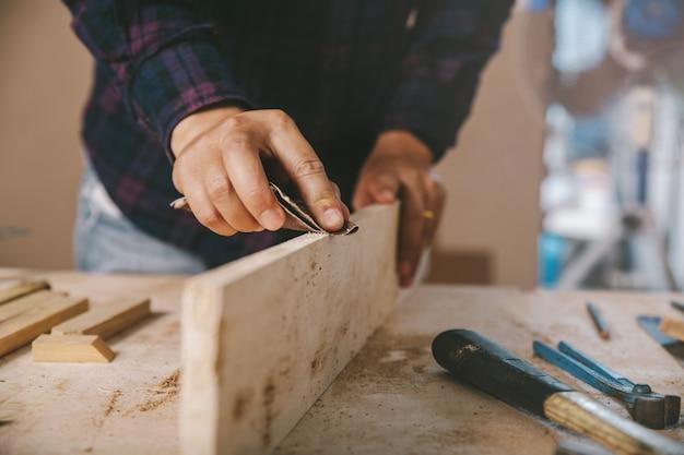 Timmerman gebruikt schuurpapier op hout. bouwnijverheid, huishoudelijk werk doe je zelf.