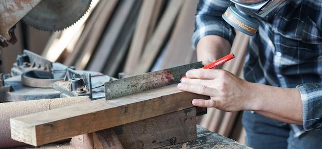 Timmerman hand bezig met houtbewerking. hout meten met liniaal en potlood