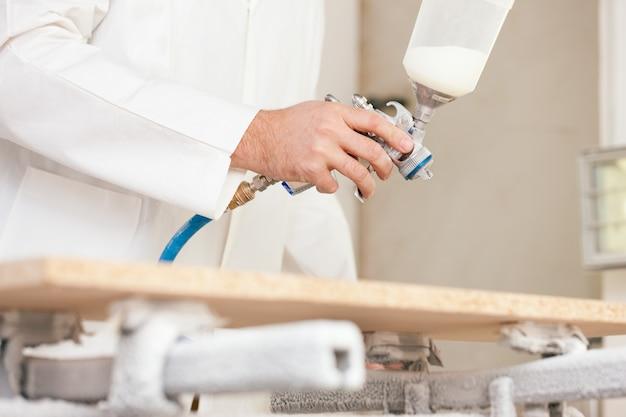Timmerman het schilderen hout met luchtpenseel