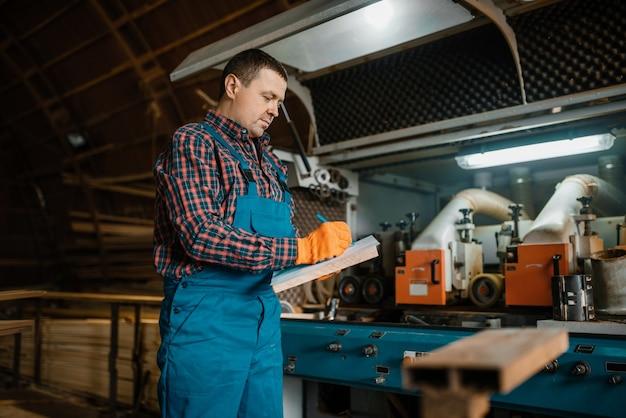 Timmerman in uniform houdt notebook, houtbewerkingsmachine, houtindustrie, timmerwerk. houtverwerking op fabriek, boszagen in houtzagerij