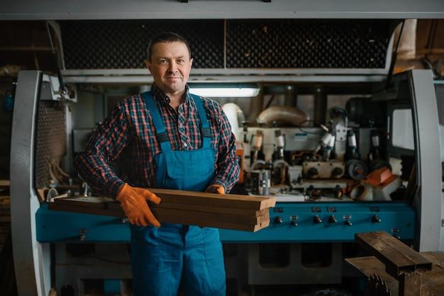Timmerman in uniform houdt planken, houtbewerkingsmachine, houtindustrie, timmerwerk. houtverwerking op fabriek, boszagen in houtzagerij