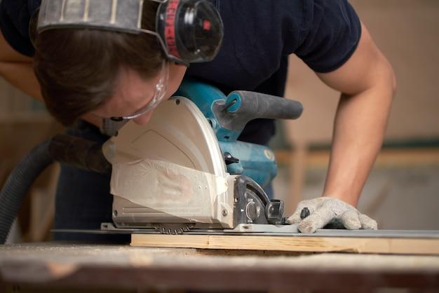 Timmerman man in witte handschoenen werkt op puzzel in werkplaats