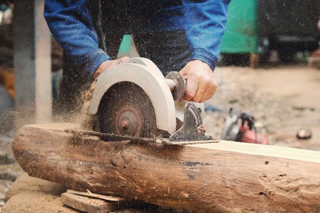 Timmerman met behulp van zagen bos snijdt op bouwplaats