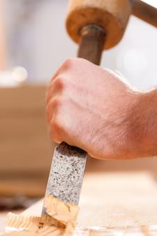 Timmerman met beitel en hamer