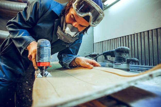 Timmerman met cirkelzaag voor het zagen van houten planken.