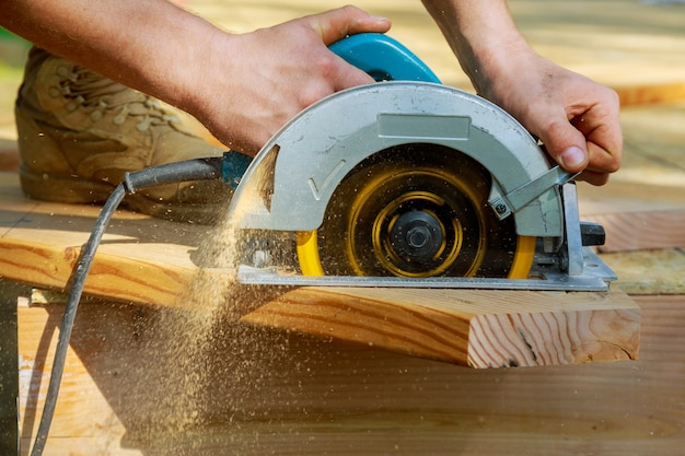 Timmerman met cirkelzaag voor houten balk een nieuw huisconstructieproject