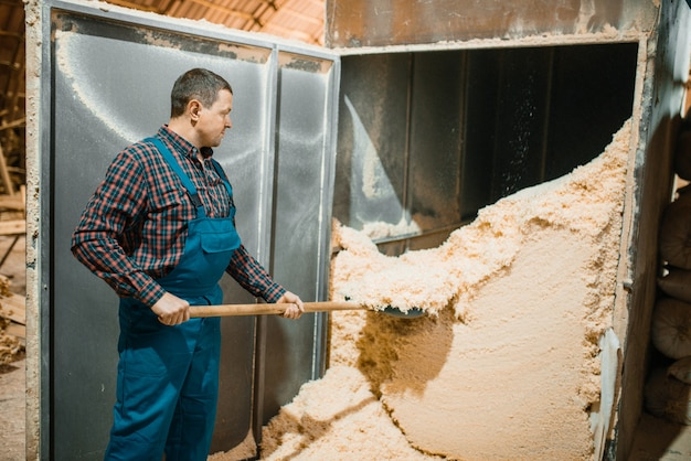 Timmerman met een schop verwijdert zaagsel, houtbewerkingsfabriek, houtindustrie, timmerwerk. houtverwerking op fabriek, boszagen in houtzagerij