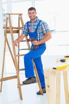 Timmerman met machtsboor die ladder beklimmen bij bouwwerf