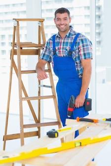 Timmerman met machtsboor die zich door ladder bij bouwwerf bevindt