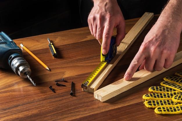 Timmerman of houtbewerker gebruikt een constructietape om de lengte van een stuk hout te meten. handen van de hoofdclose-up op het werk.