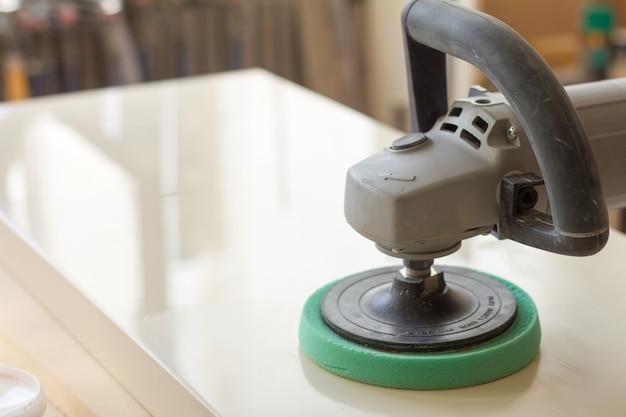 Timmerman polijst het oppervlak van de gevel voordat hij meubels monteert op een wazige timmerwerkplaats