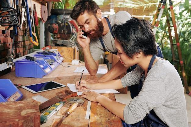 Timmerman praten over telefoon met klant wanneer zijn vrouwelijke collega details van bestelling op vel papier schrijft