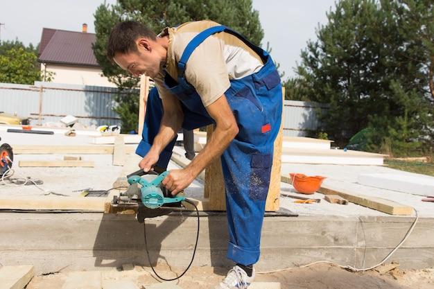 Timmerman schuren van een houten balk op een bouwplaats voor een nieuwe woningbouw