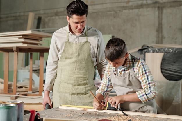 Timmerman van middelbare leeftijd in schort die zich bij bureau bevindt en let op hoe zijn tienerzoon merk op plank in workshop maakt