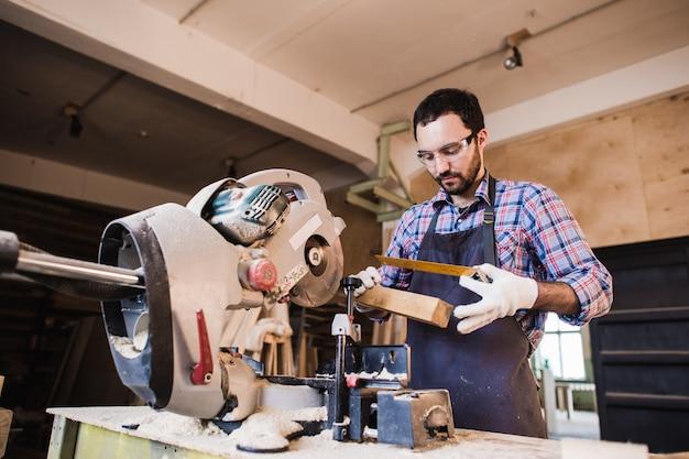 Timmerman werkt aan een elektrische cirkelzaag die sommige planken snijdt, hij draagt een veiligheidsbril