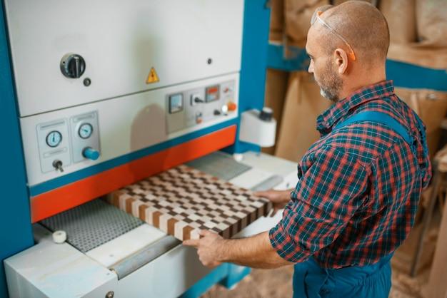Timmerman werkt aan houtbewerkingsmachine, houtindustrie, timmerwerk. houtverwerking op meubelfabriek, productie van producten van natuurlijke materialen