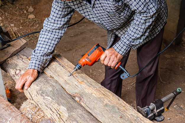 Timmerman werkt om hout te boren