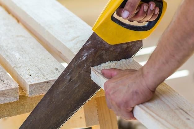 Timmermanhand met zaag die houten raad snijden