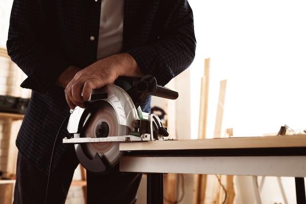 Timmermanshanden die hout zagen met elektrische zaag