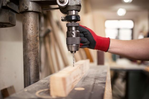Timmerwerkplaats en boormachine bezig met een stuk houtmateriaal