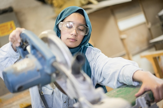 Timmerwerkplaats met professioneel moslimmeisje