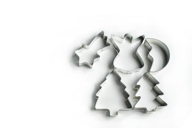 Tinnen vormen voor koekjes en peperkoek op een witte achtergrond liggen aan de rechterkant, voor uw tekst aan de linkerkant