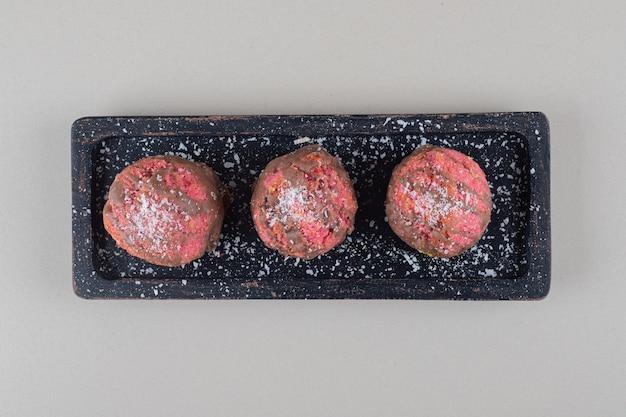 Tiny cakes op een zwart dienblad op marmeren achtergrond.