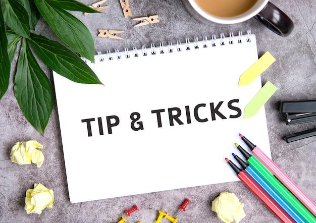 Tip en trucs op een notitieboekje met een kopje koffie, samengeperste vellen, kleurpotloden en nietmachine