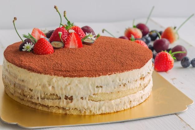 Tiramisu-cake bestrooi met cacaopoeder en versierd met vers fruit. italiaanse klassieker