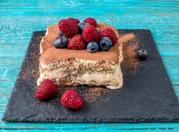 Tiramisu-cake met frambozen en bosbessen. zelfgemaakt tiramisu-dessert