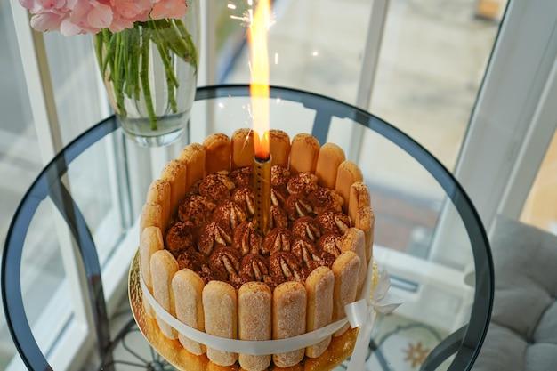 Tiramisu-cake thuis koken en decoreren door een meester voor verjaardag met een aangestoken kaars.
