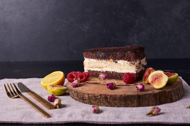 Tiramisu cake versierd met gedroogde bloemen en fruit op ronde houten plank.