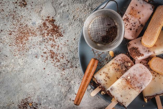 Tiramisu ijslollys ijs. gelato springt met italiaanse savoiardi-koekjes, mascarpone, melkchocolade, met tiramisu-ingrediënten op grijze stenen keukentafel. bovenaanzicht kopie ruimte