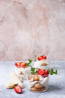 Tiramisu in een glas met verse aardbeien