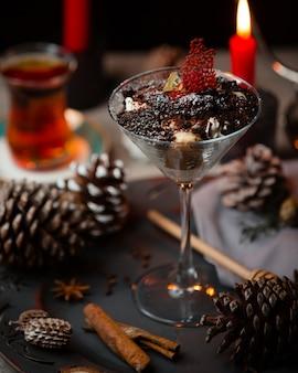 Tiramisu in martiniglas geserveerd met zwarte thee voor kersttafel