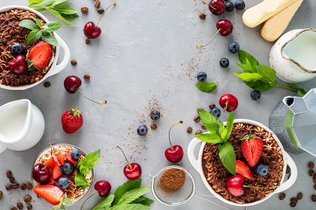 Tiramisu italiaans dessert en ingrediënten om te koken. koffie, cacao, aardbeien, munt op een witte achtergrond. kopieer ruimte bovenaanzicht
