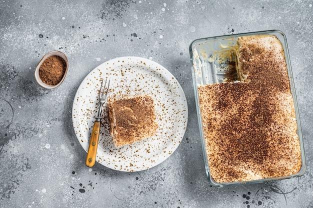 Tiramisu italiaans dessert gegarneerd met cacao op een bord. grijze achtergrond. bovenaanzicht.