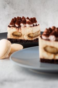 Tiramisu - klassiek dessert met mascarpone en koffie. heerlijke tiramisu-cake op een darckplaat op een lichte marmeren achtergrond. verticale foto.