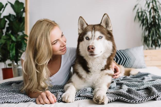 Titel mooie gelukkige vrouw met emotionele lachend gezicht liggend op comfortabel bed met schattige husky hond