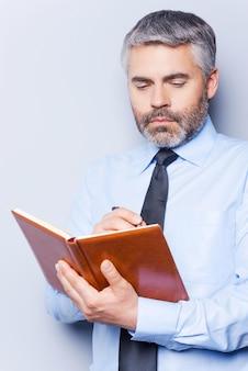 To-do lijst schrijven. zelfverzekerde volwassen man in overhemd en stropdas die iets schrijft in notitieblok terwijl hij tegen een grijze achtergrond staat