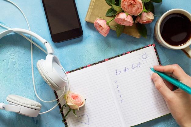 To do list concept een smartphone-koptelefoon en een open notitieboekje naast een kopje koffie