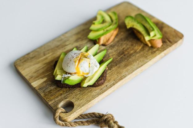 Toast, avacado sandwich en gepocheerd ei op een houten snijplank.