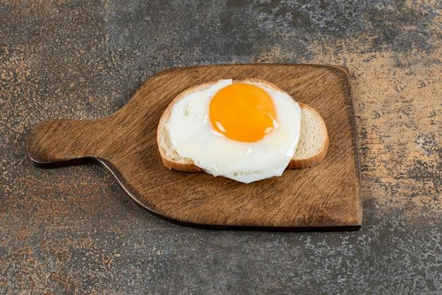 Toast brood met ei op een houten bord.