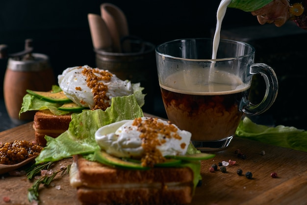 Toast brood met gesneden avocado, zakje ei en groenen op houten snijplank.