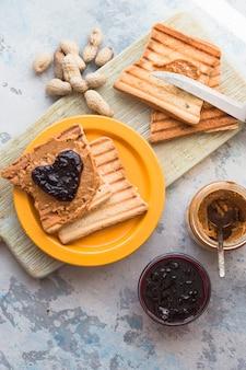 Toast brood met jam in de vorm van harten en kopje thee. gezond ontbijt met toast en fruit jam
